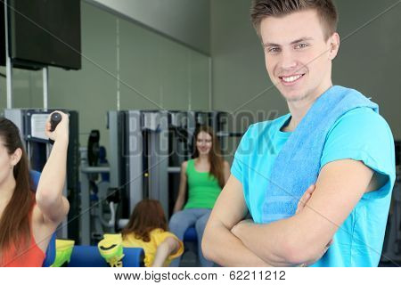 Young trainer in simulator in gym
