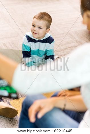 Cute boy listening to teacher in library of elementary school
