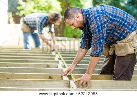 Mid adult carpenters measuring wood with tape at construction site
