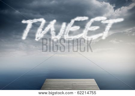 The word tweet against cloudy sky over ocean