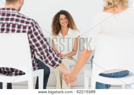 Happy therapist smiling at reconciled couple holding hands at therapy session