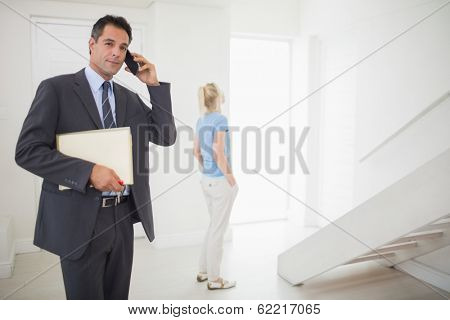 Well dressed real estate agent on call with blurred woman in the background