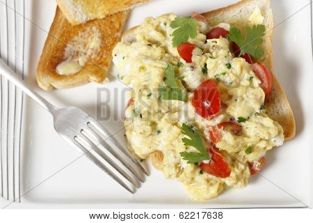 Scrambled egg on toast with cherry tomatoes, parsley and pepper. Cooking in a bain marie allows the tomatoes to be incorporated rather than curdling. From above