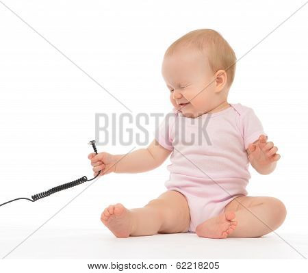 Child Baby Girl Toddler Sitting With Wire Cable Expression Of Electric Shock
