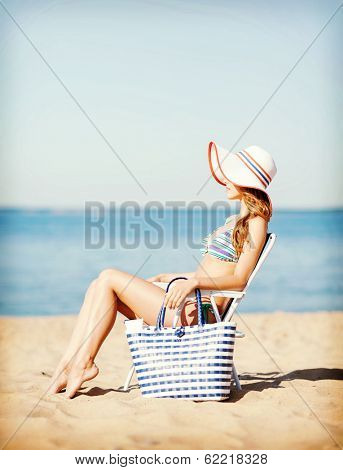 summer holidays and vacation - girl sunbathing on the beach chair