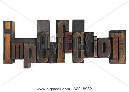 word imperfection in vintage wooden letterpress type, scratched and stained, isolated on white background