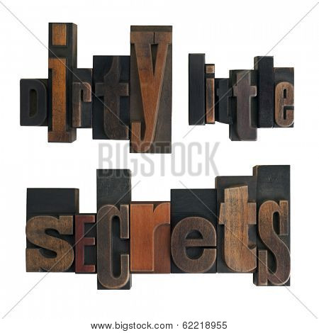 phrase dirty little secrets in vintage wooden letterpress type, scratched and stained, isolated on white background