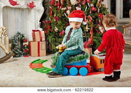 Little boy in Santa cap rides toy plastic steam engine at room decorated to Christmas celebration