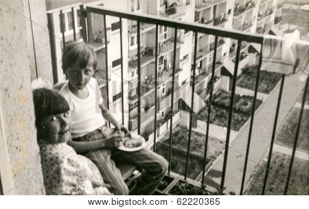 LODZ, POLAND, CIRCA 1970's: Vintage photo of siblings on balcony