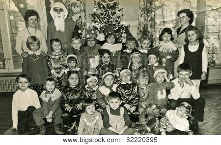 LODZ, POLAND, CIRCA DECEMBER 1970's: Vintage photo of group of little children posing with Santa Claus and their tutors