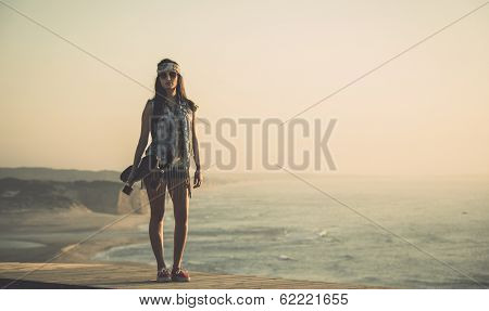 Beautiful and fashion young woman posing at the sunset with a skateboard