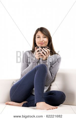 Beautiful woman sitting on the coach with a cup of coffee