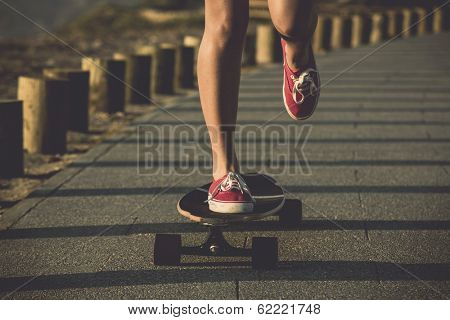 Young woman down the street with a skateboard