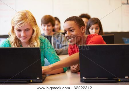 Group Of High School Students In Class Using Laptops
