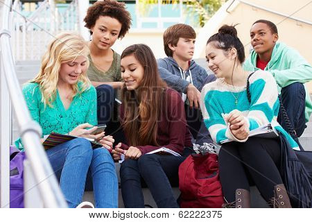 High School Students Sitting Outside Building With Phones