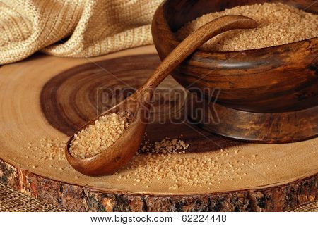 Rustic still life of vintage, handcrafted wooden bowl and spoon filled with pure cane sugar sitting on a natural acacia wooden serving tray.  Closeup with shallow dof.