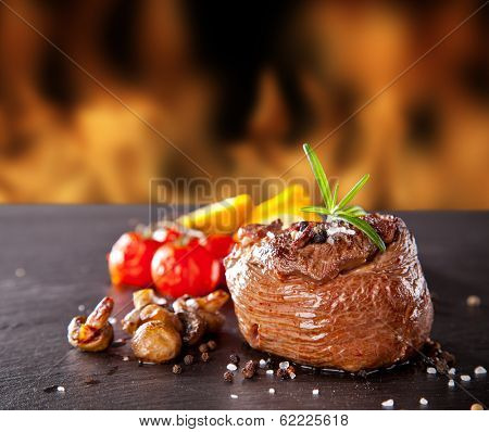 Grilled beef steak on black stone table, fire flames on background