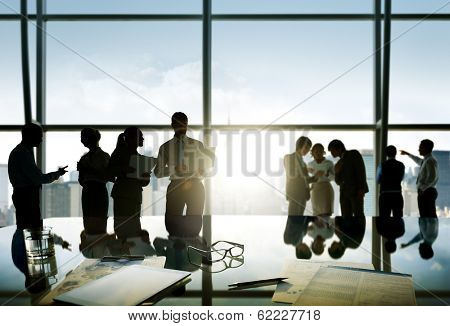 Group of business people discussing at sunrise reflected onto table with document.