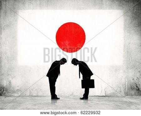 Businessmen Bowing at Japanese Flag