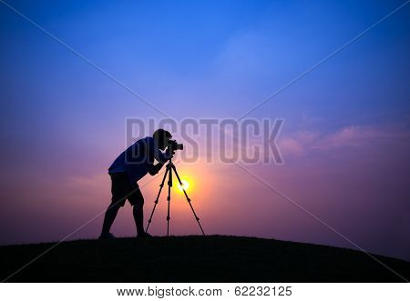 Silhouette of Young Photographer at Sunset