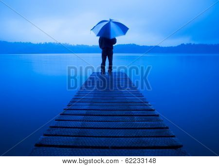 Man with Umbrella at a Pier on a Rainy Day, New Zealand