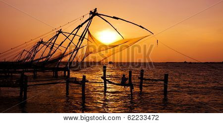 Indian Man Fishing Under The Great Chinese Nets at Cochin, Kerela, India