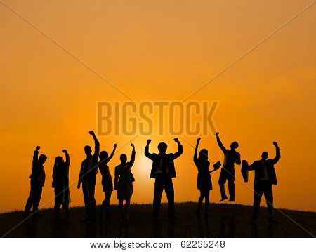 Silhouette of Business People Celebrating At Sunset