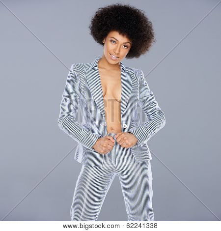 Beautiful glamorous Afro-American woman in a stylish tailored striped slack suit standing looking at the camera