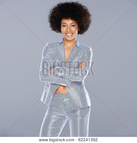 Beautiful glamorous Afro-American woman in a stylish tailored striped slack suit standing looking at the camera with folded arms and a confident amused expression