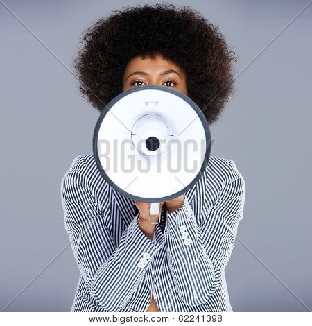 African American woman speaking into a megaphone making a public announcement with her face partially concealed, square format on grey