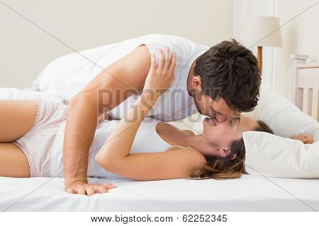 Side view of a relaxed young couple kissing in bed at home