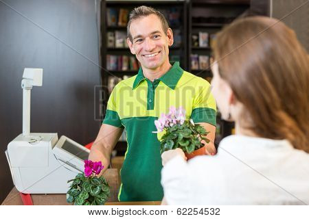 Cashier Or Shopkeeper In Flower Shop Or Retail Store Serving Client