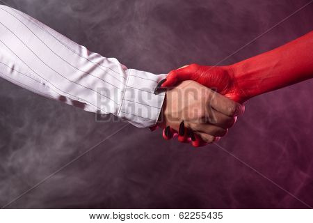 Businessman making an agreement with devil, studio shot on smoky background