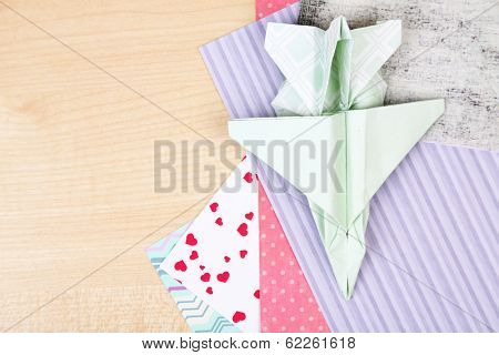 Origami airplane and color papers on wooden table