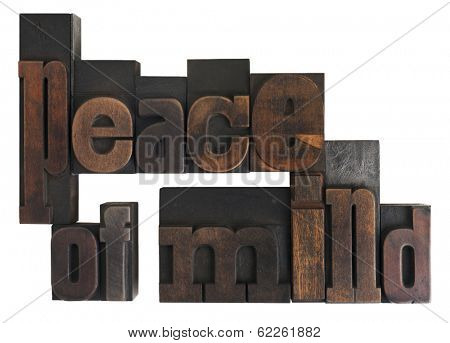 phrase peace of mind written in vintage wooden letterpress type, scratched and stained, isolated on white