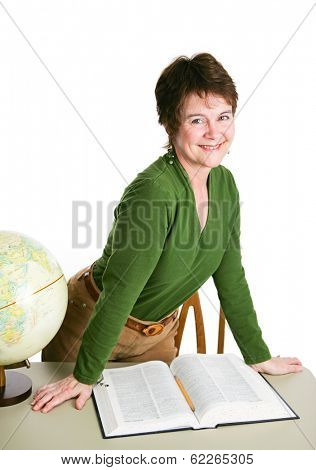 Pretty mature teacher or librarian at her desk reading a book.  Isolated on white.