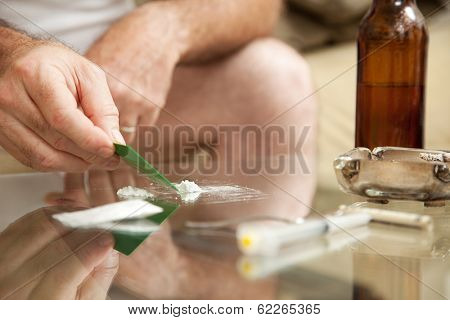 Man using powdered cocaine on a glass coffee table, with drug paraphanalia lying around.