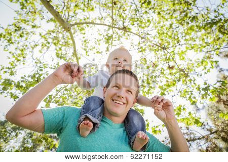 Cute Young Boy Rides Piggyback On His Dads Shoulders Outside at the Park.
