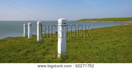 White pickets on a dike under a clear sky
