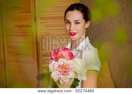 Beautiful Young Woman With A Bouquet Of Peonies Indoors