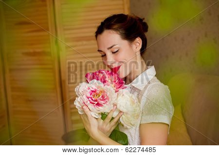 Beautiful Young Woman Smelling A Bouquet Of Peonies