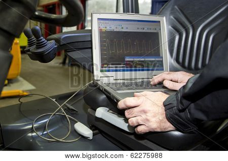 Laptop, hooked up to a forklift's engine and battery, performing various mechatronic checks, outputting the performance in a graph