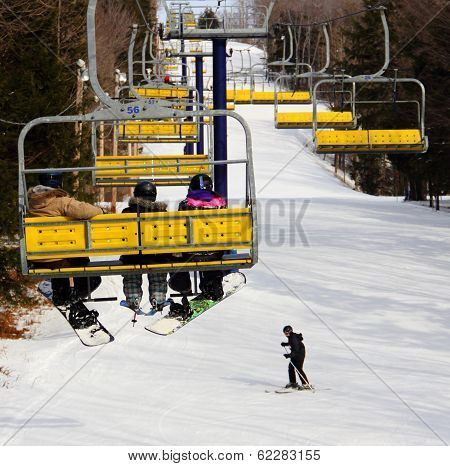 Skier & Snowboarders Going Up Mountain In Yellow Chairlift