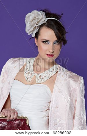 Beautiful young bride wearing vintage pastel jacket and white lace collar with flower hair band on purple studio background