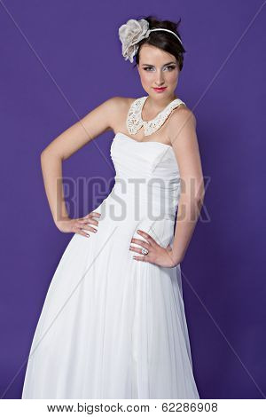Beautiful young bride wearing white dresst and white lace collar with flower band on purple studio background