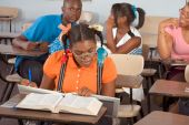 picture of girl reading book  - High school classroom with four children one boy and three girls socializing - JPG