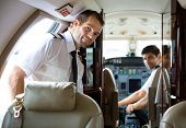stock photo of cabin crew  - Portrait of handsome pilot entering private jet with copilot in background - JPG