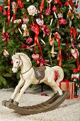 Old wooden rocking horse stands on furry rug under Christmas tree in room poster