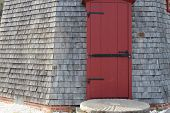 stock photo of red siding  - weathered siding with red door with black antique hinges - JPG