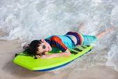 stock photo of boogie board  - Little boy on vacation having fun swimming on boogie board - JPG